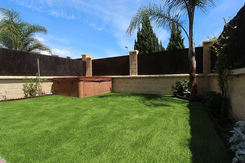 Un jardin pequeño con jacuzzi y césped artificial